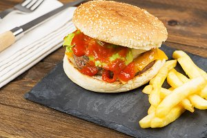Closeup of appetizing homemade burgers served on stone board with fries next to cutlery.