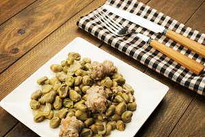 Plate with beans and sausage on wooden table.