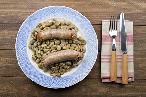 From above plate with cooked beans and sausage served on wooden table.