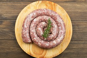 From above raw sausage with rosemary branch on wooden table.