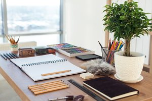 Side view of a painter workspace. Wooden desk with artistic tools prepared for pastel drawing.