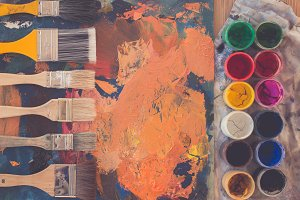 Top view close-up photo of a palette with paintbrushes and gouache paint set.