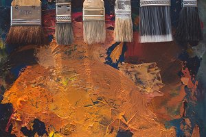 Paintbrush set lying on an old palette with oil paint brushstrokes top view photo.