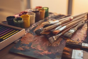Angle view photo of palette with mixed oil paints, gouache, crayons and paintbrushes set in art studio.