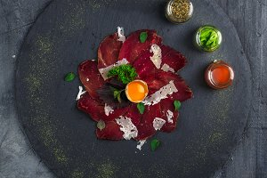 Italian Delicious Antipasto bresaola with oregano, quail egg, onion on stone plate, top view