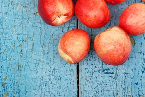 Ripe red peaches on the blue wooden table