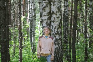 Teenager girl standing near birch in forest at summer day, portrait