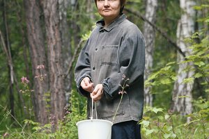 Woman in forest with bucket - picking up mushrooms