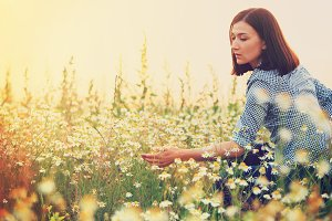 Dreaming woman looks at wild flowers