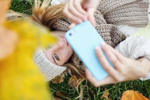 Girl doing selfie on fallen leaves