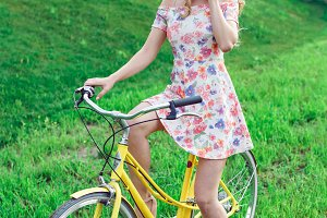Young beautiful woman with yellow bicycle in a park.