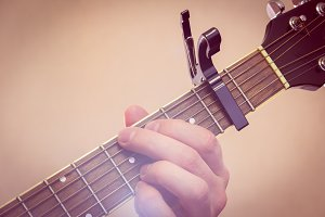 Man's hand plays the guitar