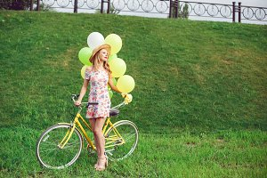 Beautiful young woman on a bicycle on a green lawn background.