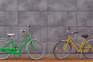 Two urban female bicycles on a gray wall background.