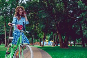 Portrait of happy smiling young woman riding a bicycle in the park.