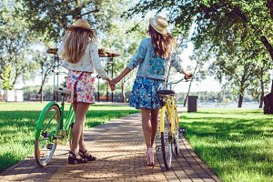 Rear view of two women holding hands walking in a park with bicycles.