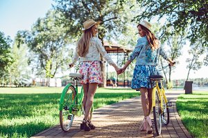 Women walking in the summer park holding hands looking in the sunset with their bikes