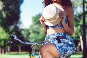 Young beautiful sexy woman in blue dress and a straw hat posing on the bike