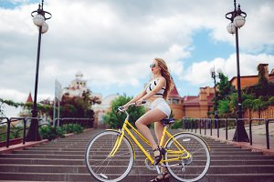 Young beautiful hipster woman in white shorts, summer trend style near beach, riding bicycle
