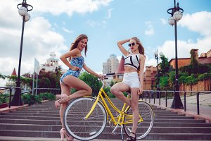 Two cheerful beautiful sexy girls, best friends posing near yellow bike.