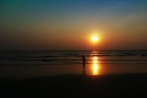 Horizontal child shadow meeting sunset on the beach bokeh backgr