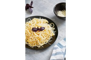 Black plate with Italian spaghetti with basil and parmesan on a gray table