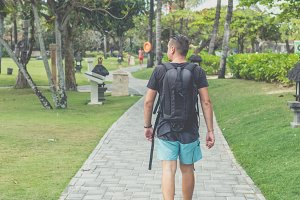Rear view of man with backpack walking in the beach park of Nusa Dua, Bali island, Indonesia.