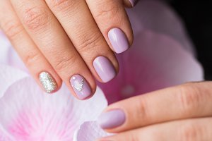 Hand with manicured nails on a pink background flowers