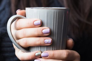 Woman with beautiful manicure holding a gray cup of tea