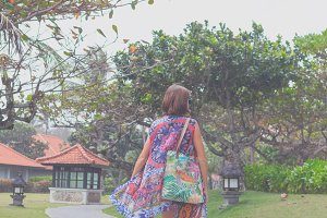 Beautiful young woman in pareo and swimsuit walking in the becah park with bag on sunny summer day. Tropical island Bali, Indonesia.