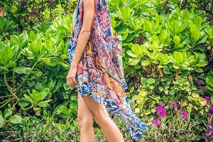 Beautiful girl in a swimsuit and pareo posing on flower background in nature of Bali island, Indonesia.
