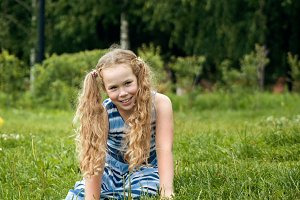 Smiling child girl wearing blue summer dress is posing in park