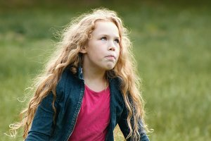 Little girl with curly hair feeling angry