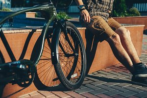 Unrecognizable young man cyclist taking out smartphone from pocket, outdoors background