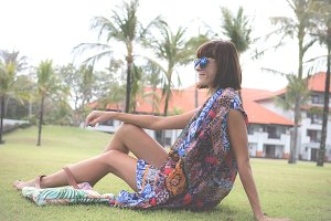 Pretty young woman in pareo and swimsuit and glasses sitting on the grass outdoors. Tropical Bali island, Indonesia.