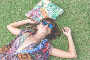 Relaxing in grass. Top view of beautiful young woman in sunglasses and pareo lying on the green grass with beach bag in the park of tropical Bali island, Indonesia.