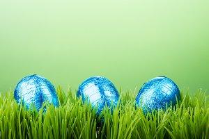 Three blue eggs in grass