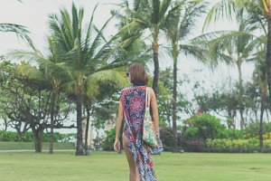 Woman walking barefoot on a tropical green field. Bali island, Indonesia. Nusa Dua park.