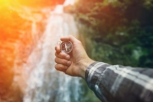 Man explorer searching direction with compass on waterfall background, point of view