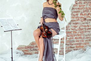 Beautiful woman holding a violin and smelling red rose
