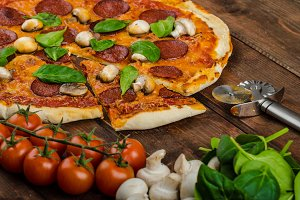 Rustic pizza with salami, mozzarella and spinach