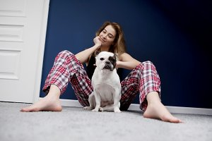 Young beautiful woman sitting with pug dog
