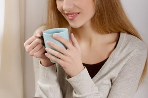 Beautiful caucasian woman drinking hot coffee or tea and looking through window.