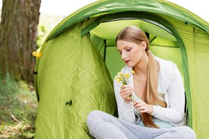Young woman resting in a tent on the nature