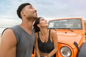 Young attractive couple looking up while standing near a car