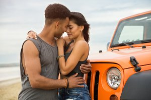 Lovely young couple kissing while standing near their car