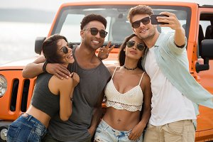 Group of young cheerful friends talking a selfie together