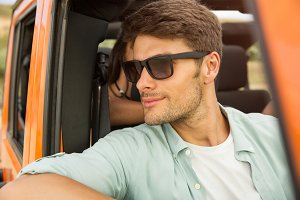 Smiling young man in sunglasses sitting on a front seat