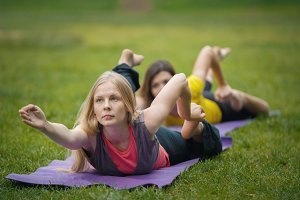 Two young women performs training for flexibility in the park