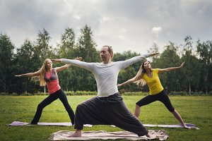 Yoga sportsmen in park - performs exercise outdoors outdoor at morning